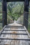 Ciérrese encima de la opinión el puente de madera y turistas en montañas de Himalaya, fotografía de archivo libre de regalías