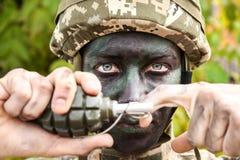 Ciérrese encima de la opinión el soldado que saca el perno de seguridad Fotos de archivo