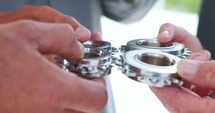 Ciérrese encima de la opinión los hombres de negocios de las manos que sostienen las ruedas metrajes