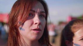 Ciérrese encima de la opinión muchachas con la bandera argentina en las mejillas que miran el juego en zona de la fan metrajes