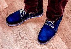 Ciérrese encima de la opinión sobre las piernas del ` s del hombre en vaqueros oscuros y las botas de cuero Foto de archivo libre de regalías