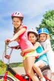Ciérrese encima de la opinión tres muchachas en la bici Foto de archivo