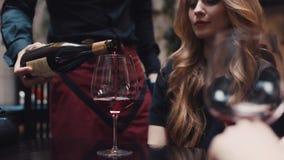 Ciérrese encima de la opinión un camarero que vierte el vino rojo en un vidrio para la mujer joven atractiva con un peinado elega almacen de video