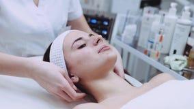 Ciérrese encima de la opinión un cosmetologist profesional joven que hace un masaje facial plástico a un paciente femenino hermos metrajes