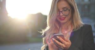 Ciérrese encima de la opinión una empresaria rubia alegre con el lápiz labial rojo que practica surf Internet vía su smartphone,  metrajes