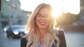 Ciérrese encima de la opinión una mujer rubia caliente atractiva en vidrios, con el lápiz labial rojo haciendo una pausa la mirad almacen de video