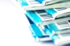Ciérrese encima de la parte del código de barras en la revista azul que apila con pizca Foto de archivo libre de regalías