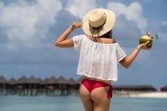 Ciérrese encima de la parte posterior de la muchacha en bikini contra la playa y el coco del océano Imagen de archivo libre de regalías