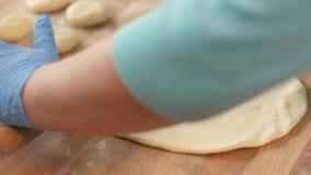 Ciérrese encima de la pasta de la pizza del balanceo del panadero en la tabla antes de cocer en restaurante metrajes
