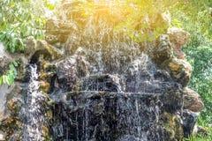 Ciérrese encima de la pequeña cascada en el jardín Foto de archivo libre de regalías