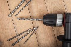 Ciérrese encima de la perforadora, destornillador con los taladros en la tabla de madera Preparado para los agujeros de perforaci Imagen de archivo