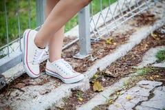 Ciérrese encima de la pierna del ` s de la muchacha de la moda de los jóvenes en la zapatilla de deporte blanca calzado para el d Foto de archivo libre de regalías