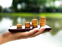 Ciérrese encima de la pila de monedas del dinero en el teléfono móvil, negocio en concepto del comercio electrónico Imagenes de archivo
