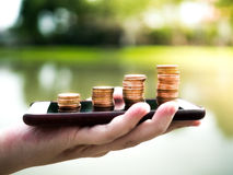 Ciérrese encima de la pila de monedas del dinero en el teléfono móvil, negocio en concepto del comercio electrónico Foto de archivo