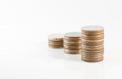 Ciérrese encima de la pila de monedas en el fondo blanco para financiero y el sa Imagen de archivo libre de regalías