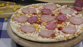 Ciérrese encima de la pizza cruda que gira en la tabla, desde arriba almacen de metraje de vídeo