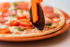 Ciérrese encima de la pizza de los cortes del cuchillo circular foto de archivo libre de regalías