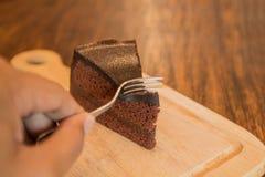 Ciérrese encima de la rebanada de torta de chocolate con el frok en la tabla de madera Imagenes de archivo