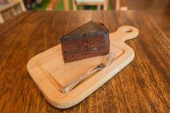 Ciérrese encima de la rebanada de torta de chocolate con el frok en la tabla de madera Imagen de archivo libre de regalías