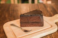 Ciérrese encima de la rebanada de torta de chocolate con el frok en la tabla de madera Fotos de archivo libres de regalías