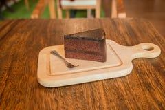 Ciérrese encima de la rebanada de torta de chocolate con el frok en la tabla de madera Imagen de archivo