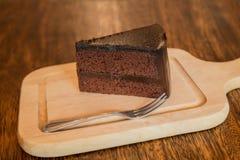 Ciérrese encima de la rebanada de torta de chocolate con el frok en la tabla de madera Imágenes de archivo libres de regalías
