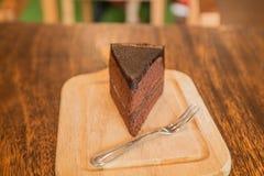 Ciérrese encima de la rebanada de torta de chocolate con el frok en la tabla de madera Fotos de archivo