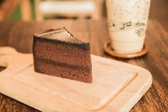 Ciérrese encima de la rebanada de torta de chocolate en la tabla de madera Imagen de archivo