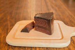 Ciérrese encima de la rebanada de torta de chocolate en la tabla de madera Imagenes de archivo