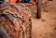 Ciérrese encima de la rueda pesada del camión de la suciedad del neumático de coche del camino con la cadena o Foto de archivo libre de regalías
