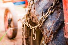 Ciérrese encima de la rueda pesada del camión de la suciedad del neumático de coche del camino con la cadena o Foto de archivo