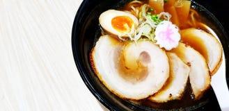 Ciérrese encima de la sopa de fideos caliente de los ramen, del cerdo cortado, de la yema de huevo y de la cuchara blanca en cuen imagen de archivo libre de regalías
