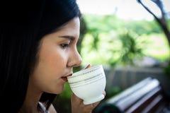Ciérrese encima de la taza de café de consumición de la mujer joven en parque público fotografía de archivo libre de regalías