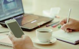 Ciérrese encima de la taza de café y de ordenador portátil con la mano del hombre de negocios que usa el teléfono elegante Foto de archivo libre de regalías
