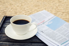 Ciérrese encima de la taza del café con leche en la tabla de madera en la playa de la arena de la salida del sol con el periódico Fotos de archivo