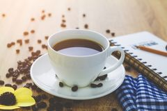 Ciérrese encima de la taza del café con leche en la tabla de madera marrón cerca de ventana Imagenes de archivo