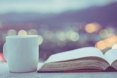 Ciérrese encima de la taza del café con leche y del libro viejo en b contrario y colorido Imagen de archivo libre de regalías