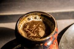 Ciérrese encima de la taza negra y roja del vintage con café Imagenes de archivo