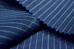 Ciérrese encima de la tela azul marino del traje Imagenes de archivo