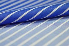 Ciérrese encima de la tela azul y blanca del rollo de la camisa Fotos de archivo