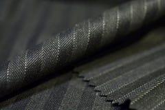 Ciérrese encima de la tela gris y negra del rollo del traje Imagen de archivo