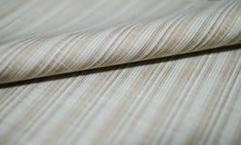 Ciérrese encima de la tela marrón brillante del rollo del traje Imagen de archivo libre de regalías