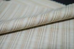 Ciérrese encima de la tela marrón brillante del rollo del traje Imágenes de archivo libres de regalías