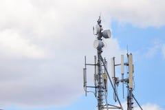 Ciérrese encima de la torre blanca del repetidor de la antena del color en el cielo azul Fotos de archivo