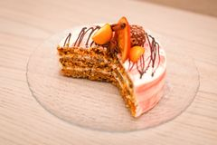 Ciérrese encima de la torta cremosa deliciosa con el chocolate, rebanadas anaranjadas, palillo de canela en la tabla con el corte Fotografía de archivo