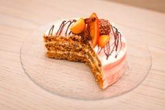 Ciérrese encima de la torta cremosa deliciosa con el chocolate, rebanadas anaranjadas, palillo de canela en la tabla de madera co Imagen de archivo libre de regalías