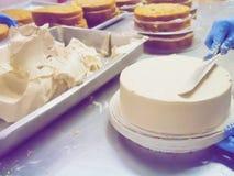 Ciérrese encima de la torta que hace en industria de la torta con el filtro del vintage Foto de archivo