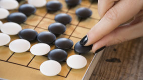 Ciérrese encima de la vista de la mano femenina que juega pedazos de piedra blancos y negros en chino van tablero del juego Imagenes de archivo