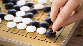 Ciérrese encima de la vista de la mano femenina que juega pedazos de piedra blancos y negros en chino van tablero del juego Fotos de archivo libres de regalías