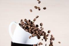 Ciérrese encima de la vista de la taza blanca que se coloca en la taza negra con caer abajo los granos de café asados marrón Imagen de archivo libre de regalías